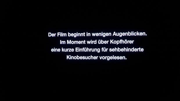 Ein Text informiert die Kinobesucher, dass vor dem Filmstart eine Adiointroduktion über Kopfhörer ausgegeben wird und der Film in Kürze beginnt