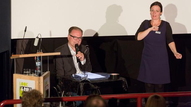 Moderator Alex Oberholzer wird von einer Gebärdensprachdolmetscherin übersetzt