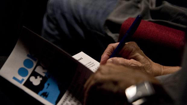 Die Hände einer Besucherin beim Ausfüllen der Teilnahmekarte für den Publikumspreis