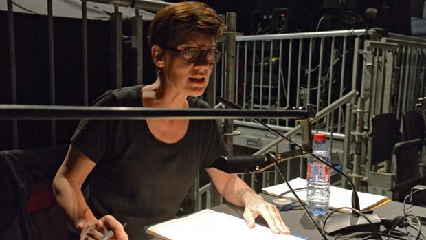 Eine Frau spricht die Audiodeskription in ein Tischmikrofon