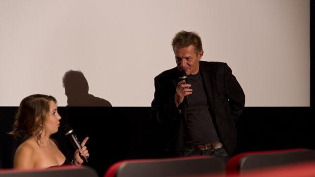 Eine sehr kleine Frau und ein Mann mit Mikrofonen vor der Kinoleinwand