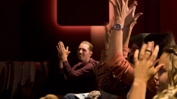 Gäste mit Hörbehindrungen bekunden mit erhobenen Händen Beifall