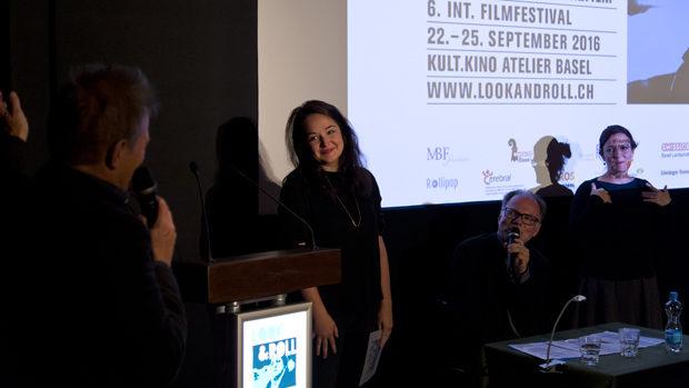 Kim Faber, eine junge Frau von etwa 30 Jahren bei der Preisverleihung vor der Leinwand