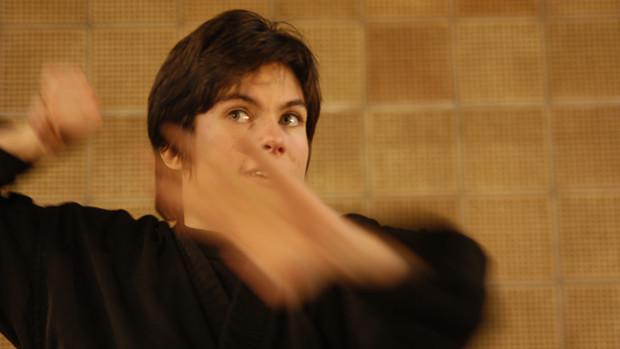 Farbiges Halbportrait einer jungen Frau beim Karate-Training