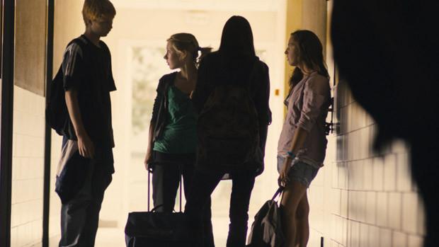 Eine Gruppe von drei Schülerinnen und einem Schüler im Gang des Schulhauses