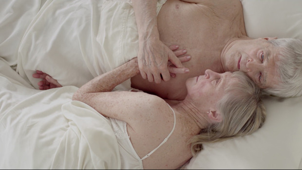 An elderly couple lying embracing each other lying on a bed