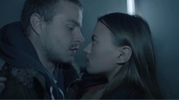 Ein junger Mann und eine junge Frau sehen sich verliebt an und stehen im Begriff, sich zu küssen