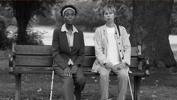 Two women with white canes sitting on a bank in a park