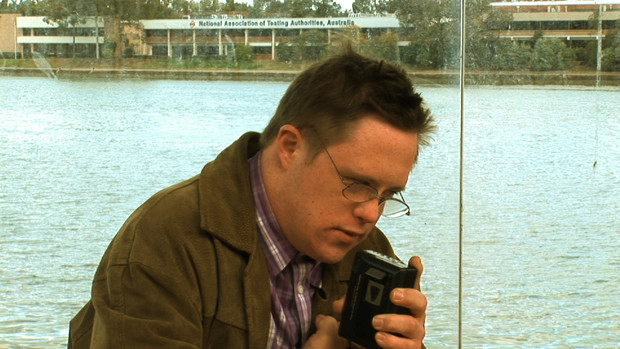 A young man with down syndrome recording himself with a dictaphone at a bus stop