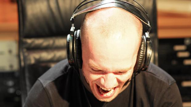 Ein junger Mann mit Kopfhörern im Tonstudio