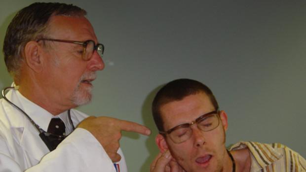Ein Arzt deutet auf das Ohr eines ängstlichen jungen Mannes.