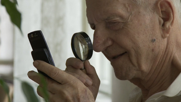 An elder man reads on the display of his mobile using a magnifying glass