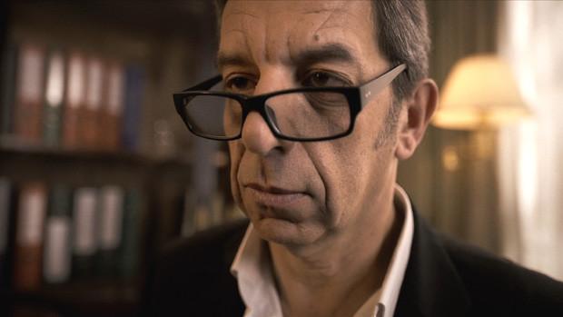 Das Gesicht eines Mann in einer Praxis, der über seine Brille hinweg in den Rau sieht