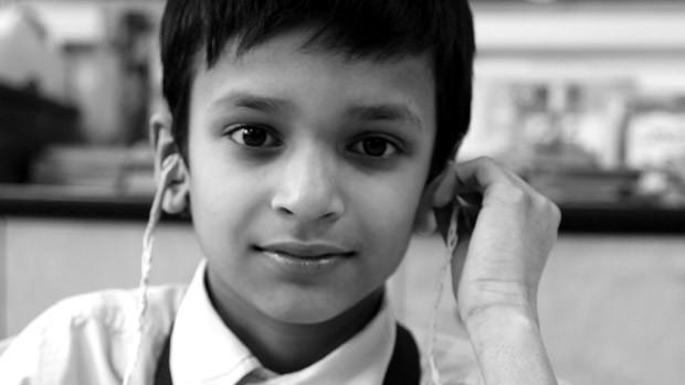 Gesicht eines kleinen Jungen mit einem altmodischen, grossen Hörgerät
