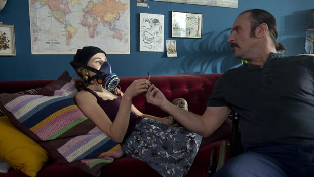 Ein Mann im Rollstuhl reicht einer jungen Frau mit Gasmaske, die auf dem Sofa sitzt einen Joint.