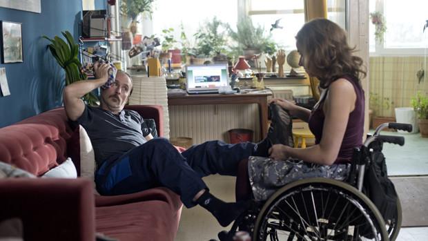 Eine junge Frau im Rollstuhl massiert einem auf der Couch liegenden Mann die Füsse