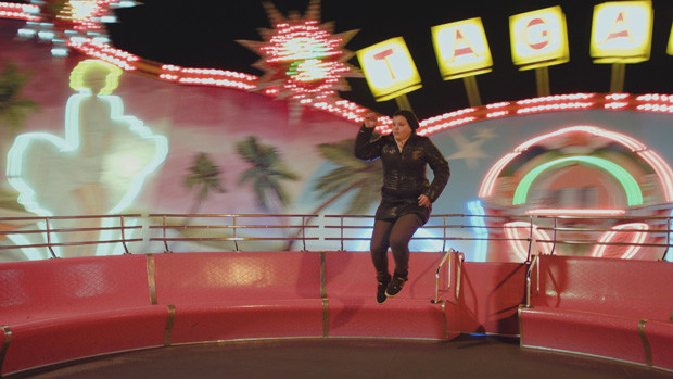 A girl making a jump in the middle of a running carousel