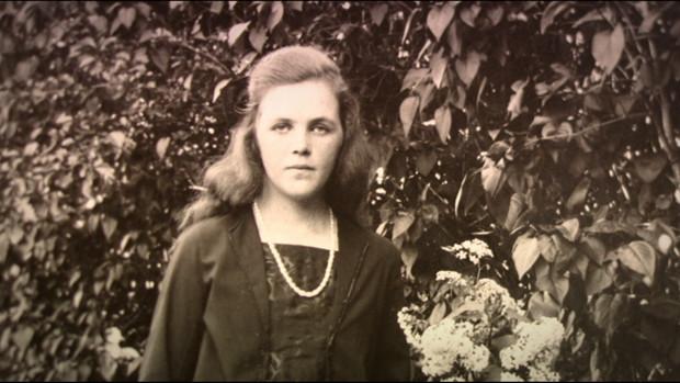 Ein altes Schwarzweissfoto einer jungen Frau im Garten