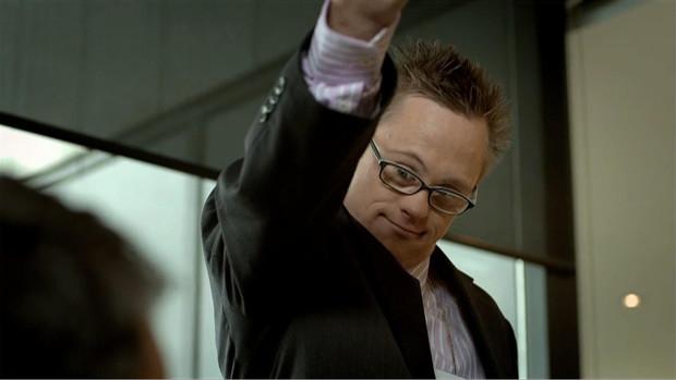 Ein Geschäftsmann mit Downsyndrom fordert einen Bewerber mit erhobenem Arm auf, sich zu erheben
