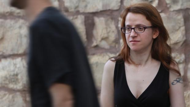Eine junge Frau blickt einem vorübergehenden Mann interessiert hinterher