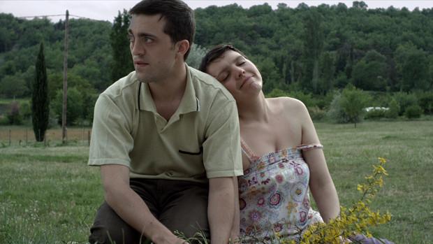 Ein Paar mit Lernbehinderungen kniet aneinandergelehnt auf einer Wiese