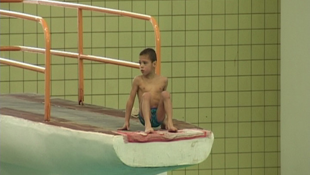 A boy sitting at the edge of the 10m-tower of a swimming pool