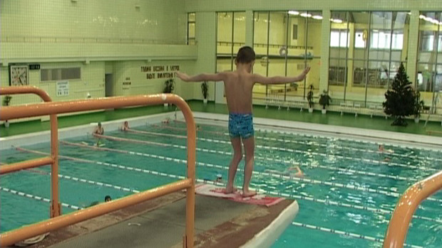 Ein kleiner gehbehinderter Junge an der Absprungkante eines Dreimeterbrettes