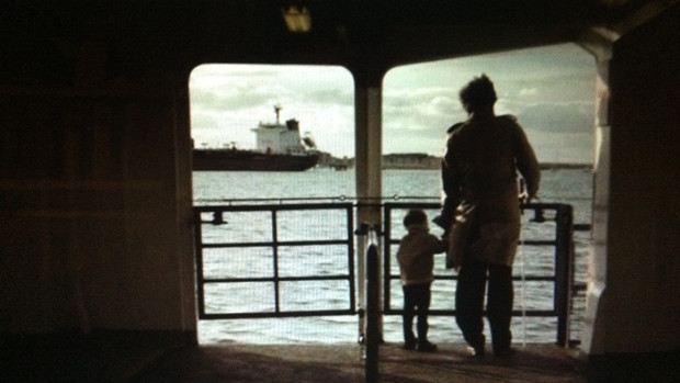 A man and his little son watching the sea from board of a ferry