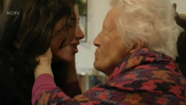 An old woman kisses a young girl