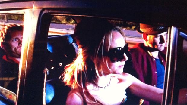 Ein vollbesetzter Oldtimer mit einer Frau mit Sonnebrille am Steuer
