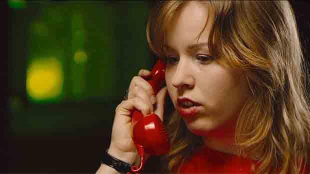 Eine junge blonde Frau hält einen roten Telefonhörer an ihr Ohr