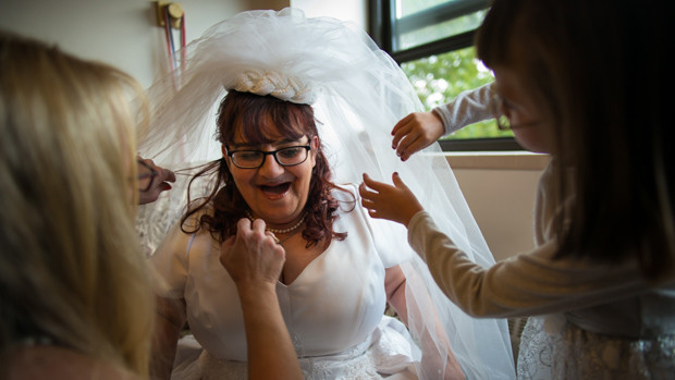 Two women fixing the veil on a bride's head.