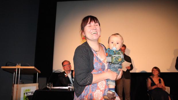 Eine junge Frau mit einem Kleinkind auf dem Arm lacht strahlend ins Publikum