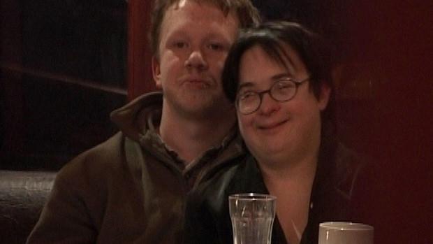 Ein lernbehindertes Paar sitzt Arm in Arm lächelnd in  einem Café