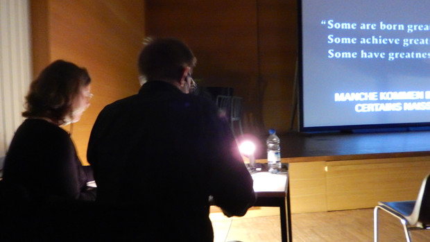 Die Sprecher einer Live-Audiodeskription vor der Leinwand, auf der ein Filmbild zu sehen ist