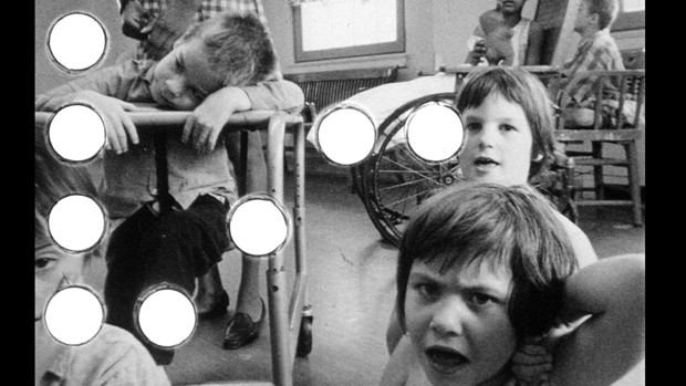Black and white film still of a group of small children gazing into the camera with grim and curious faces