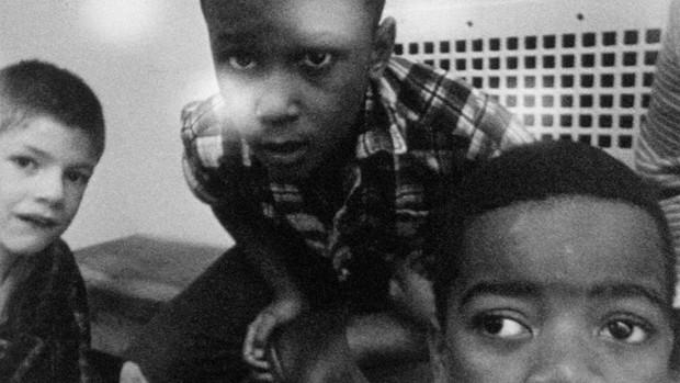 Schwarzweissbild: Drei kleine Jungs schauen neugierig in die Kamera