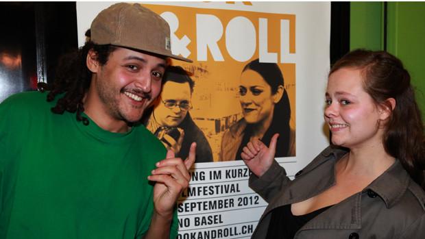 Eine junge Frau und ein junger Mann posieren vor einem Festivalplakat