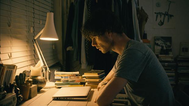 Ein junger Mann sitzt abends vor seinem Notebook am Schreibtisch
