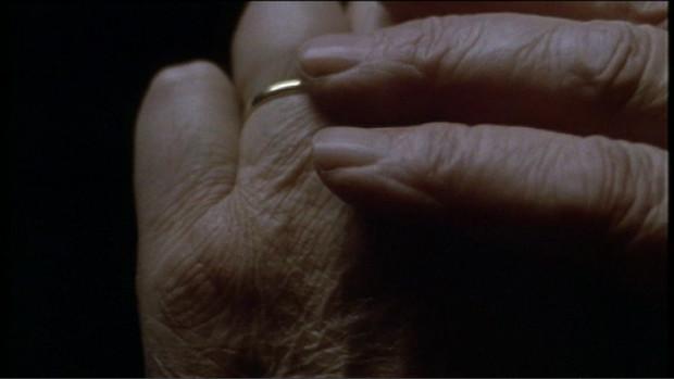 Finger einer rechten Hand streichen über den Ehering einer Frau