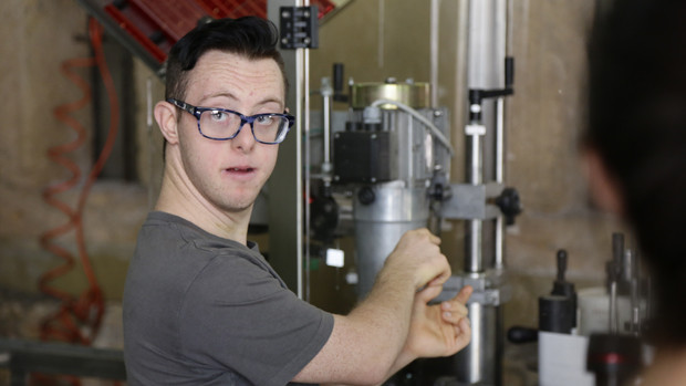 Ein junger Mann mit Trisomie 21 bei der Arbeit an einer Abfüllmaschine