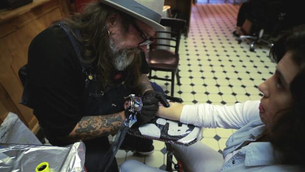 Eine junge Frau lässt sich den Unterarm tätowieren.