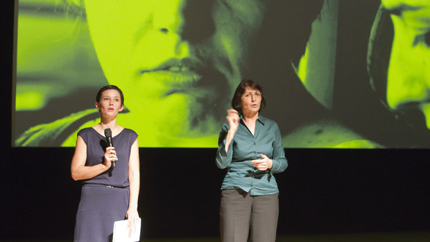 A young woman with short dark hair moderating in company of a sign language interpreter