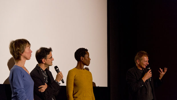 The three guests talking to festival director Gerhard Protschka in front of the screen
