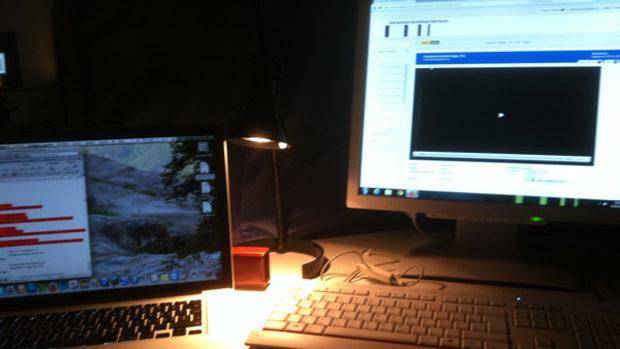 Zwei Computerbildschirme in einer abgedunkelten Sichtungsbox