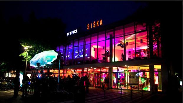 Die bunt beleuchtete Fensterfront des Kino Šiška in der Dunkelheit