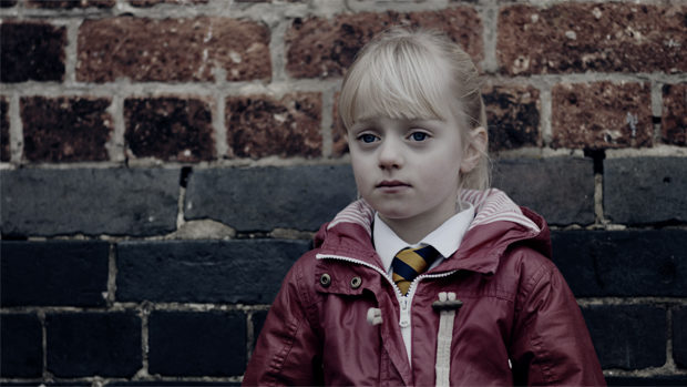 4 year-old Libby leaning with sad eyes at wall of her pre-school building