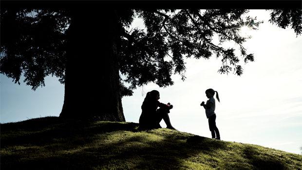 Eine junge Frau und ein kleines Mädchen im Schatten eines grossen Baumes