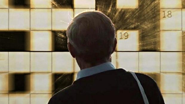 Ein Mann mkit dem Rücken zur Kamera blickt auf ein grosses Kreuzworträtsel an der Wand vor ihm