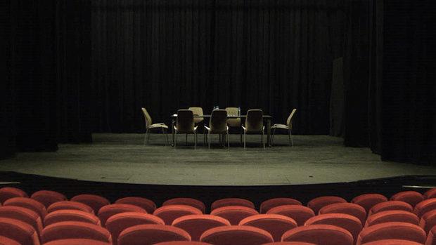 Ein Besprechungstisch mit 6 Stühlen auf der Bühne eines menschenleeren Theaters